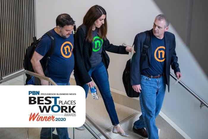 Nelnet is a Top Workplace in Rhode Island - three Nelnet associates wearing Circle N t-shirts walk side by side through an office