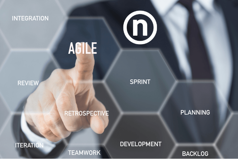 Agile Framework at Nelnet - A man in a suit points to the word Agile on a touchscreen
