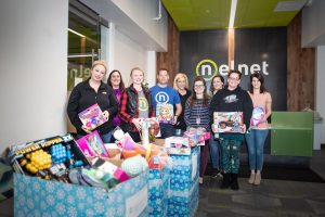 Nelnet associates posing in front of toys from charity drive