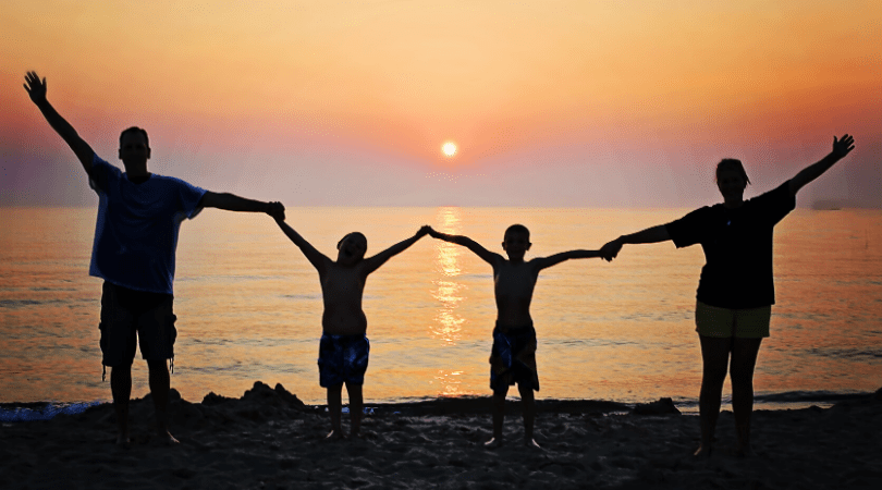 Family practicing social distancing on a beach at sunset