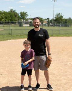 Nelnet associate and his son posing on baseball diamond