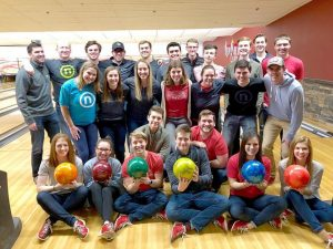 Nelnet associates at bowling alley posing with bowling balls